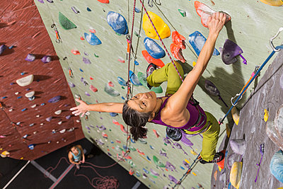 Mother belaying daughter climbing rock wall - p555m1312136 by Don Mason
