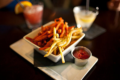 Close up of bowl of french fries in restaurant - p555m1421179 by Kyle Monk