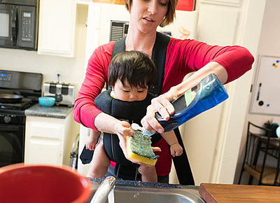Mother with baby in carrier, washing dishes - p924m1155141 by Raphye Alexius