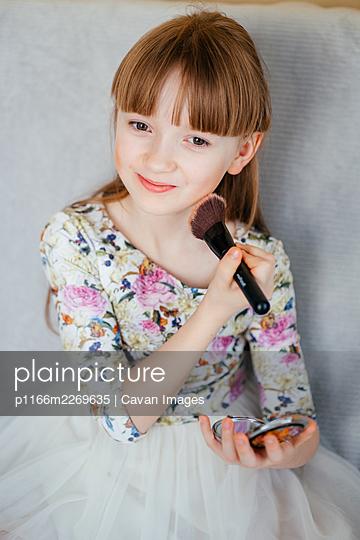 girl secretly does makeup at home - p1166m2269635 by Cavan Images