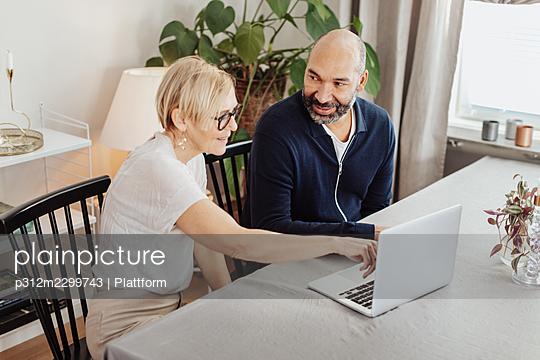Couple using laptop at home - p312m2299743 by Plattform