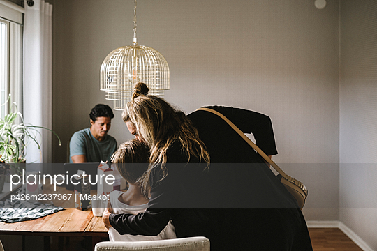 Mother kissing son over dining table at home - p426m2237967 by Maskot