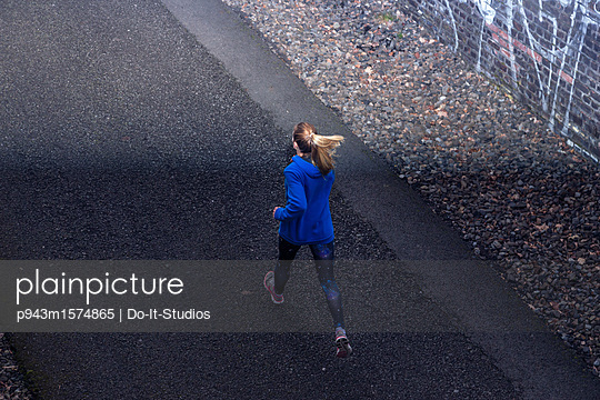 Young woman jogging on asphalt - p943m1574865 by Do-It-Studios