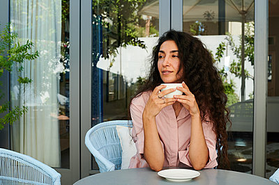 Woman drinking coffee on the terrace, portrait - p1640m2254624 by Holly & John