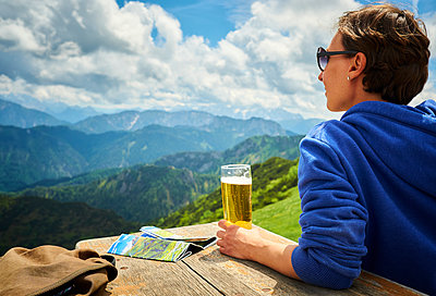 Germany, Chiemgau, hiker on Hochfelln Mountain with glass of beer looking at view - p300m1470079 by Dirk Kittelberger