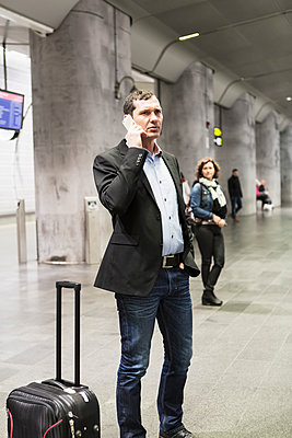 Businessman using mobile phone while standing at railway station - p426m1085305f by Kentaroo Tryman