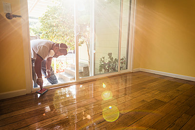 Hispanic man refinishing floors in new house - p555m1408523 by Sollina Images