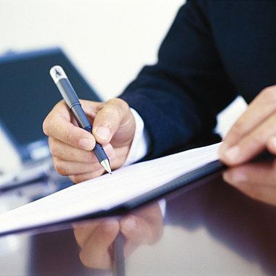 Businessman signing document at desk - p62317802f by Vincent Hazat