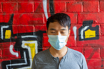 Young man with community mask against graffiti - p975m2207622 by Hayden Verry