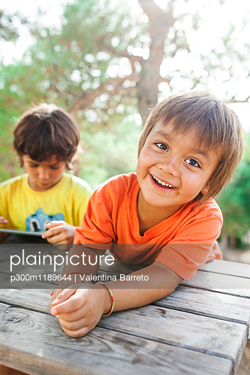 Portrait of relaxed little boy with his brother using tablet in the background