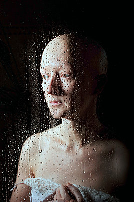 Woman with alopecia behind pane with waterdrops - p1019m2149526 by Stephen Carroll