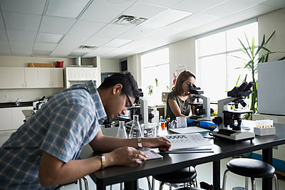 College students conducting scientific experiment in science laboratory - p1192m1145692 by Hero Images