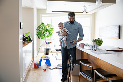 Father with baby working from home - p1192m2088297 by Hero Images