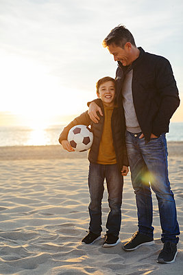 Father embracing son with football on the beach at sunset - p300m1562292 by Bonninstudio