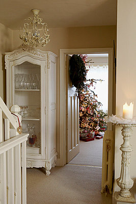 Christmas wreath on open door with painted white glass fronted cabinet - p349m789729 by Brent Darby