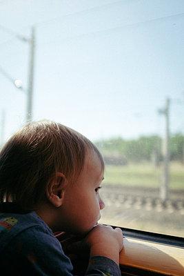 Baby boy gazing out train window - p795m2223680 by JanJasperKlein