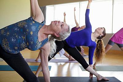 Females stretching yoga class - p924m821494f by Natalie Faye