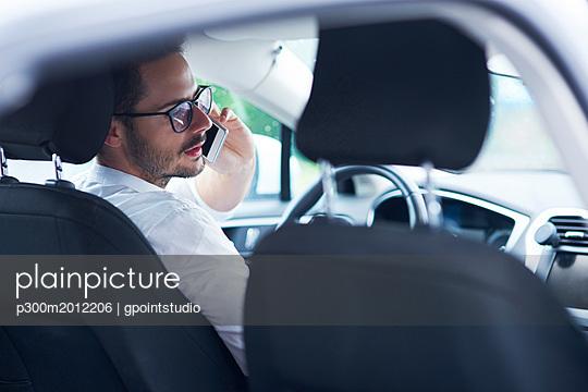 Businessman sitting in car talking on the phone - p300m2012206 von gpointstudio