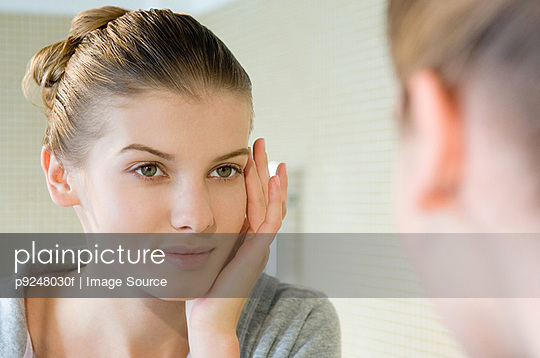 Woman touching face - p9248030f by Image Source