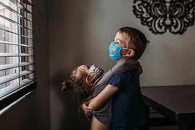 Lifestyle portrait of young siblings with masks on hugging at home - p1166m2207801 by Cavan Images