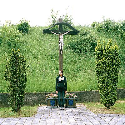Junge Frau vor Jesuskreuz - p1199m1004393 von Claudia Jestremski