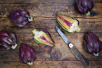 Sliced and whole purple organic artichokes and a pocket knife on dark wood - p300m1205679 by Larissa Veronesi