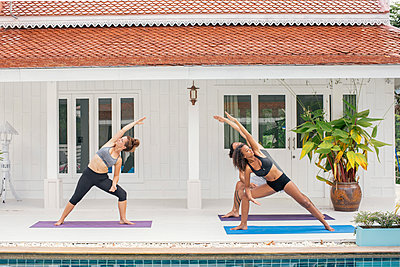 Two women and a man practicing yoga on terrace - p300m1587815 von Mosu Media