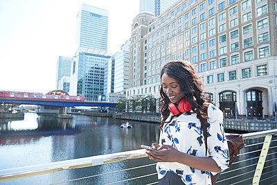 Businesswoman with backpack and headphones using mobile phone while standing on bridge in city - p300m2241631 by Pete Muller