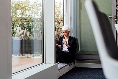Entrepreneur using mobile phone while sitting on doorway - p300m2282386 by Eugenio Marongiu