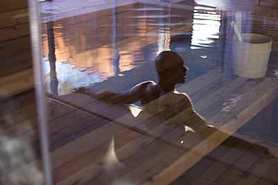 Man relaxing in swimming pool, reflected on glass door - p623m1086504f by Anne-Sophie Bost