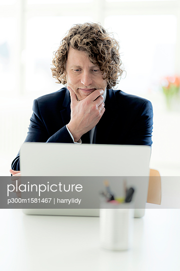 Businessman using laptop at his desk - p300m1581467 von harrylidy