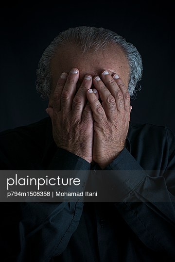 Elderly man hiding face with hands  - p794m1508358 by Mohamad Itani