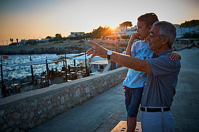 Italy, Santa Caterina, grandfather and grandson looking at view by sunset - p300m1505246 by Dirk Kittelberger