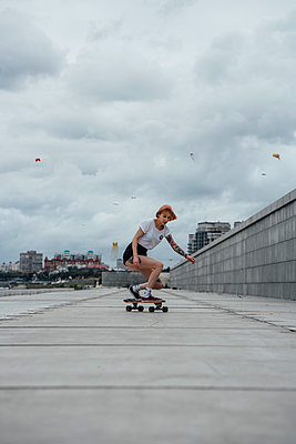 Young woman riding carver skateboard on a promenade - p300m2059464 by Vasily Pindyurin