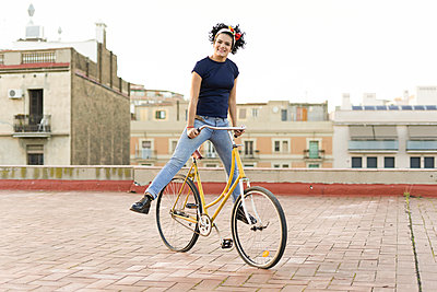 Portrait of happy young woman balancing on bicycle in the city - p300m2079617 by Eloisa Ramos