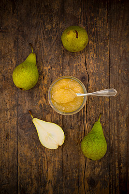 Whole and sliced organic pears and glass of pear jam on dark wood - p300m977836f by Larissa Veronesi