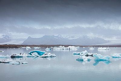 Iceland, Asturland, Vatnajokull National Park, Ice floe on Jokulsarlon lake with snowcapped mountain range on horizon - p352m1349364 by Gustaf Emanuelsson