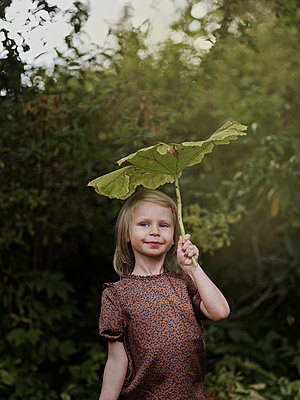 Girl with leaf above head, Varmdo, Uppland, Sweden - p528m875619 by Anna Kern