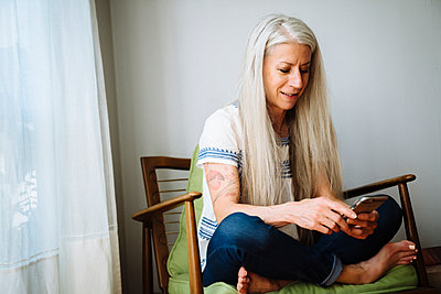 Caucasian woman sitting in armchair texting with cell phone - p555m1305096 by Inti St Clair photography
