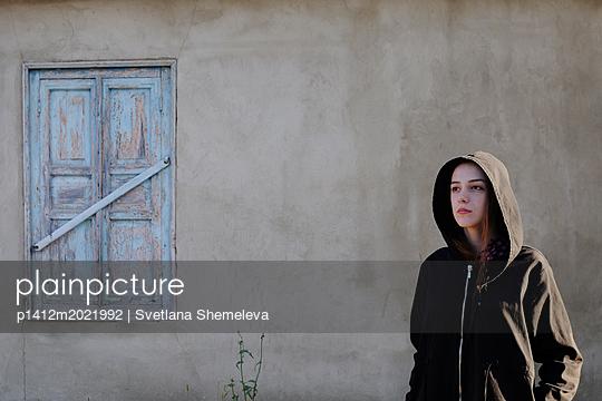 Frau vor einem Fenster mit geschlossenen Fensterläden - p1412m2021992 von Svetlana Shemeleva