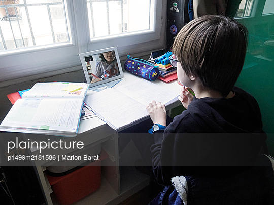 Boy doing homeworks with schoolfriend on Facetime during Covid-19 quarantine - p1499m2181586 by Marion Barat