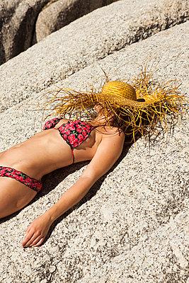 Frau sonnt sich auf Felsen - p045m1444885 von Jasmin Sander