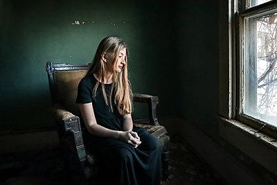 Mädchen in schwarzem Kleid auf altem Sessel - p1019m2142909 von Stephen Carroll