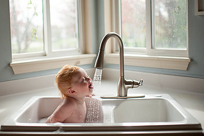 Cute baby boy sticking out tongue under running water from faucet in kitchen sink - p1166m1512515 by Cavan Images