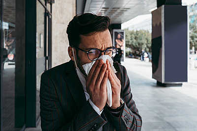 Sick man with protective face mask coughing and sneezing on street. - p1166m2179397 by Cavan Images