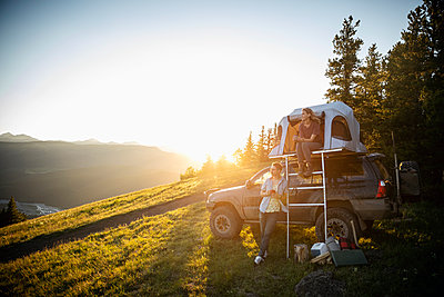 Couple camping, relaxing at SUV rooftop tent in sunny, idyllic field, Alberta, Canada - p1192m2016496 by Hero Images