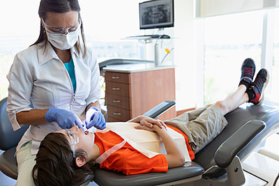 Dental hygienist flossing teeth of boy in dentist office - p1192m2033567 by Hero Images