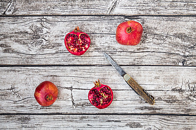Two whole and two halves of organic pomegranate and a pocket knife on wood - p300m1120812f by Larissa Veronesi