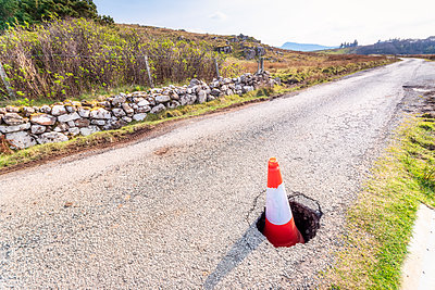 Traffic cone in pot hole on road at Isle of Skye, Highlands, Scotland, UK - p300m2144351 by Scott Masterton