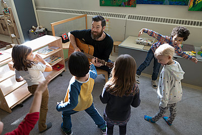 Preschool students dancing, listening to male teacher playing guitar in classroom - p1192m1560124 by Hero Images